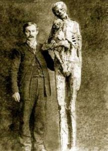 A man posing with a giant mummified corpse